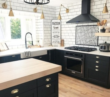 Black Cabinet And Light Natural Wood Countertop Kitchen With White Brick Walls And Gold Furnishings