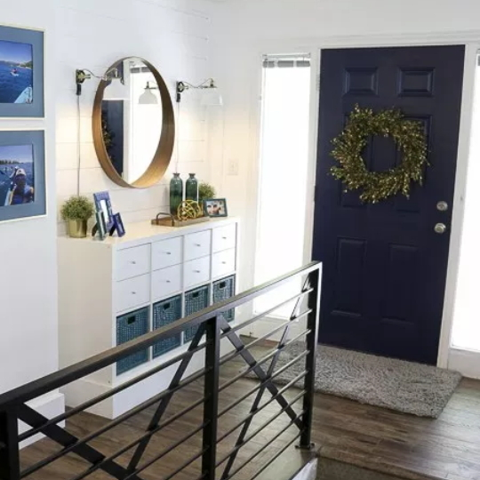Entry Shot With Metal Railing, Wooden Floor, Dark Blue Front Door, Green Wreath, White Table With Pops Of Blue And Gold Accents