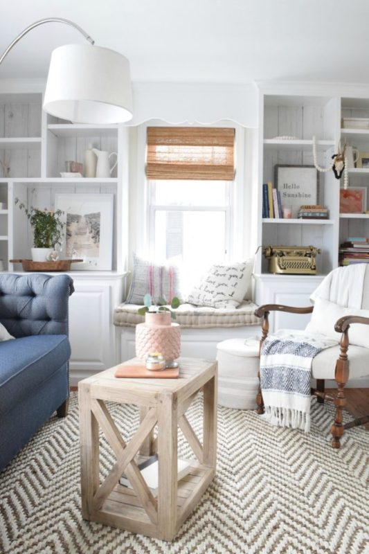 Square Wooden Table With X On Each Side, White Living Room Walls, Blue Couch, White And Blue Striped Blanket On White Chair