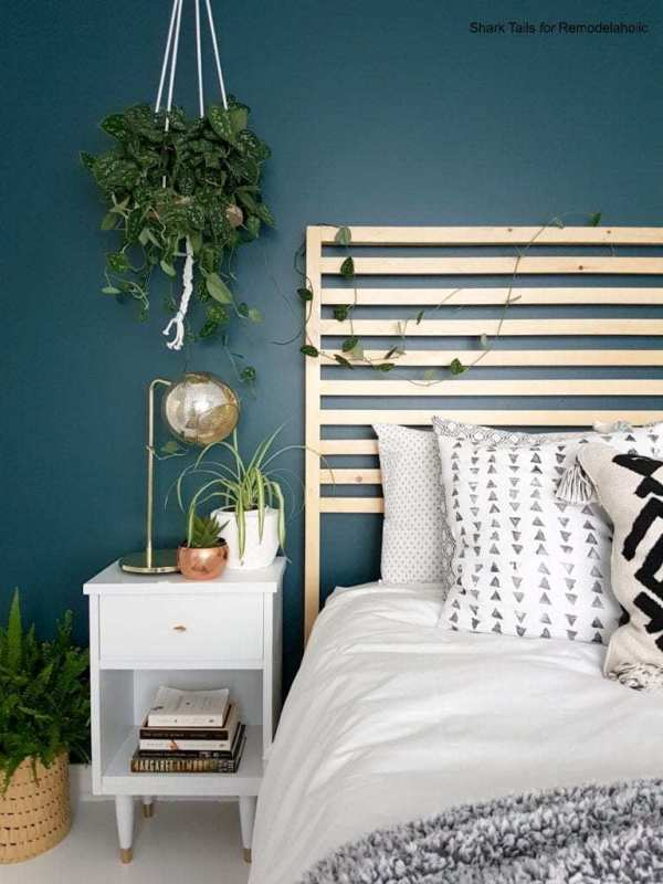 Blue Wall With Natural Wood Headboard, White Bedding, Patterned Pillows And Hanging Plant From The Ceiling, White Nighstand With Gold Accented Light And Planter