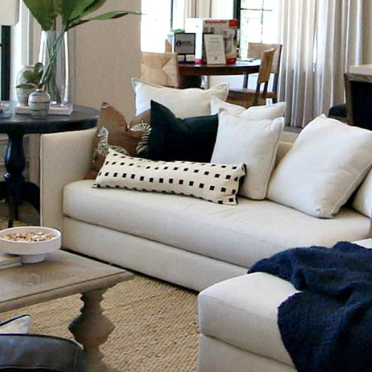 Cream Couches With Navy And Patterned Pillows, Natural Wood Table