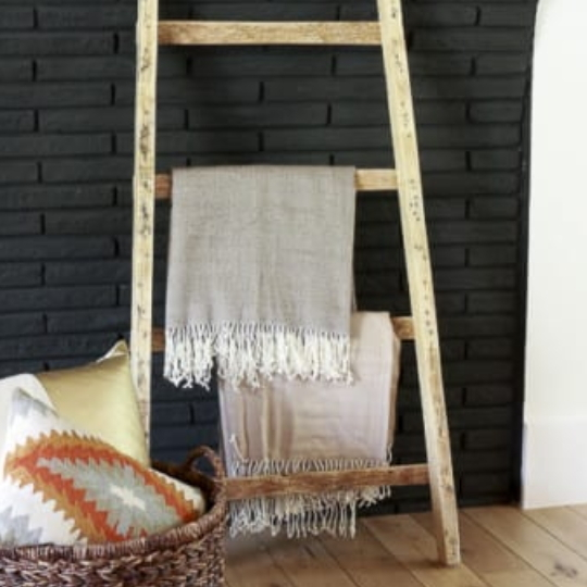 Black Brick Wall With Natural Wood Blanket Ladder Leaning Against It