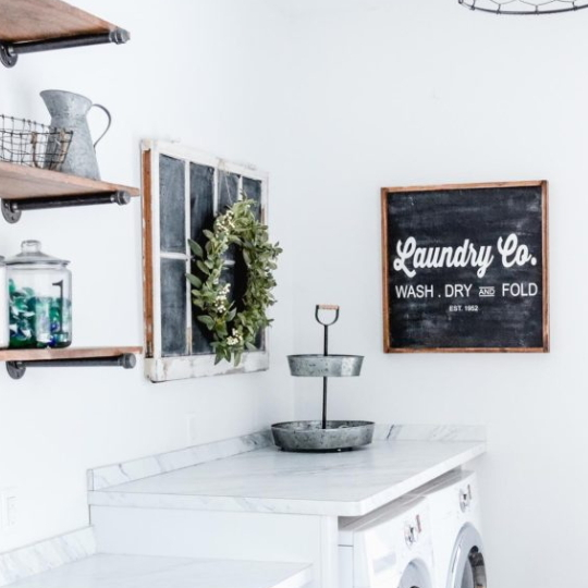 Laundry Room With White Walls, Wooden Shelves, Faux Window And Laundry Co Chalkboard Sign