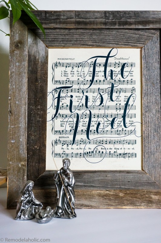 Rustic Wooden Frame With Vintage Music And The First Noel Written Across In Calligraphy