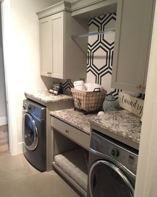 Washroom With Front Loading Washer And Dryer With Counterspace On Top, Different Levels, Drawers, Cupboard And Hanging Rod And Accent Wall With Patterned Wallpaper