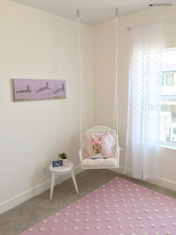 Little girls room with a wicker swinging chair, with a cute pink bunny pillow. SLPH 2018 Home 5 Regal Homes, photo by Remodelaholic.com