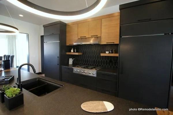 Modern Dark Gray Kitchen Cabinets With Light Wood Upper Cabinets, Black Tile Backsplash, UVPH House 27 Emerald Homes