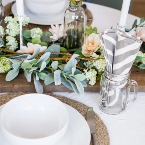 Tablescape Image With White Dishes, Glass Mason Jar Cup, Striped Napkins, And Floral Bouquet