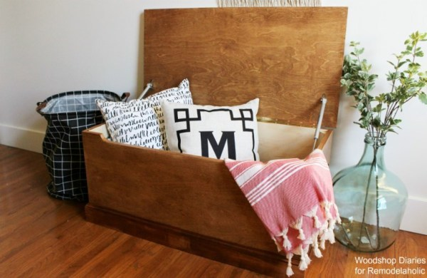 Simple DIY Wooden Storage Chest Plans Tutorial With Pillows And Blanket Hanging Out Of Open Top