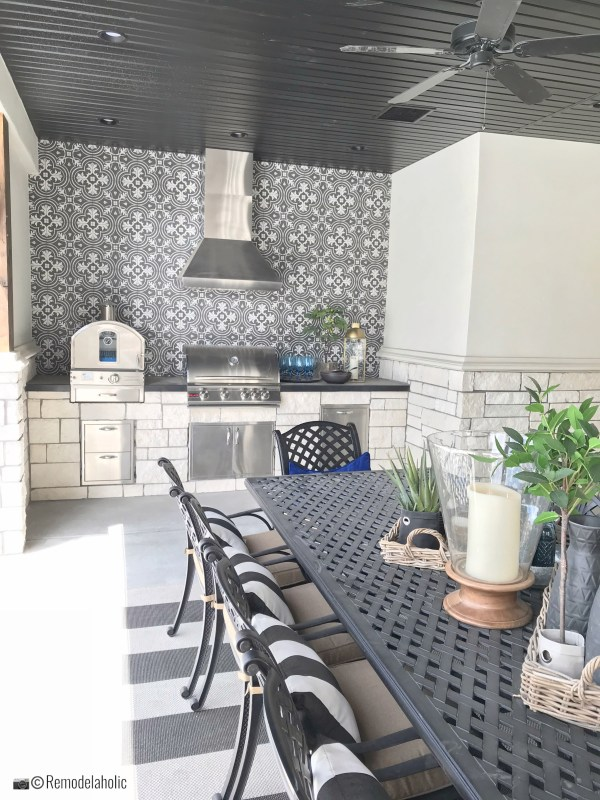 Outdoor kitchen area with dining table and cute pillows. UVPH 2018 Home 30 Shelby Homes, Gatehouse No. 1 Furniture & Design, Photo by Remodelaholic
