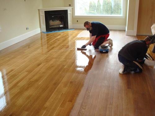 Contractors refinishing hardwood floor