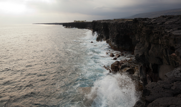 The ocean crashing up against the lava rocks.