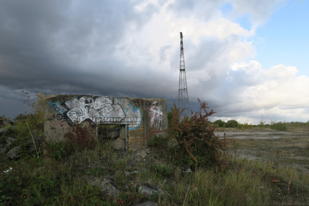 A derelict WW2 bunker on Swanscombe Peninsula, with a very tall electricity pylon in the background.