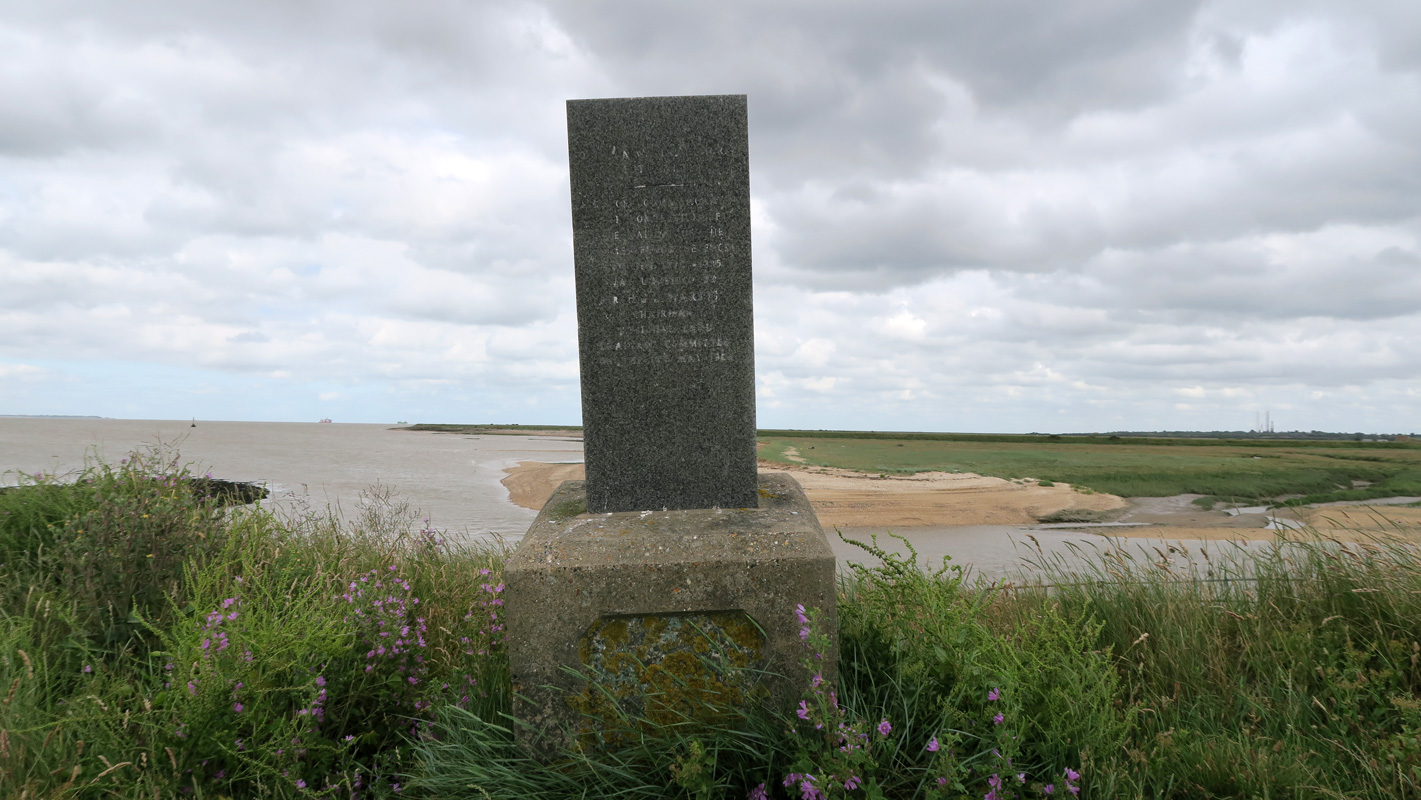 A dark square pillar rises higher than a man, with faded writing on it. Behind it, the estuary landscape is one of water and low marsh.