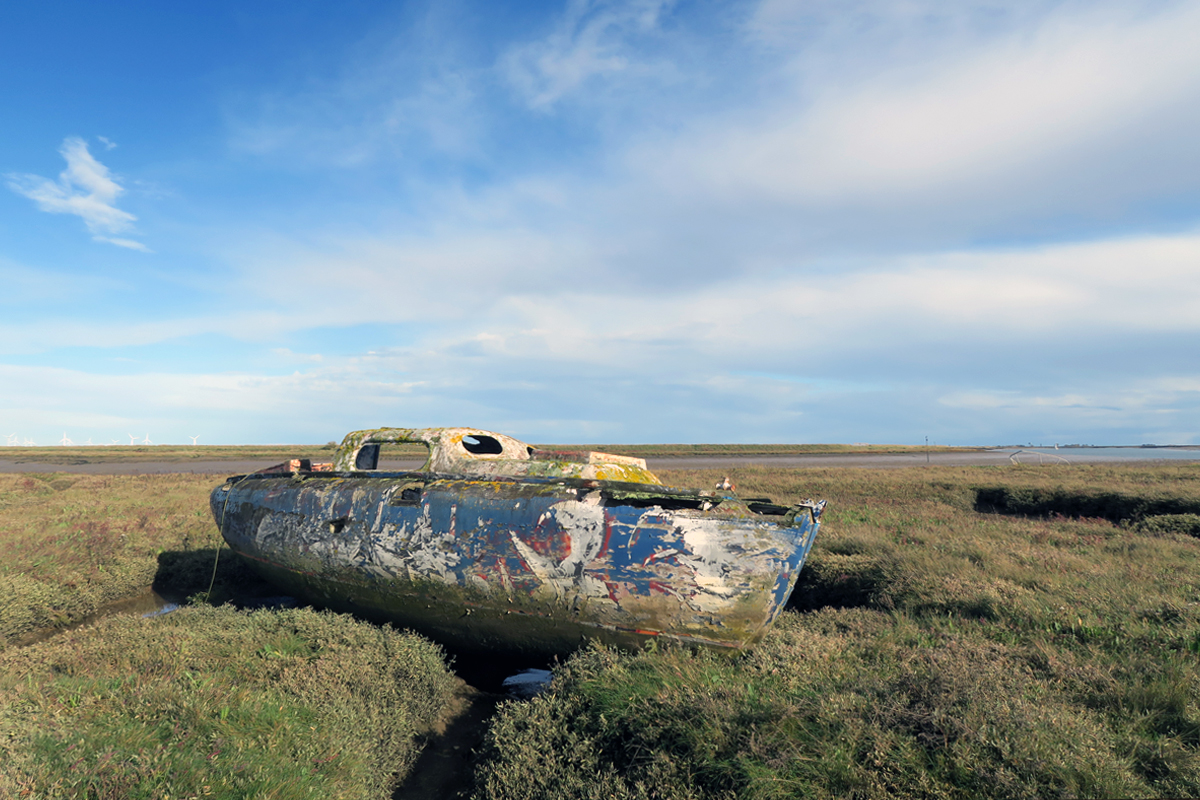 A scarred sailboat body resting on the saltmarsh at Paglesham Creek