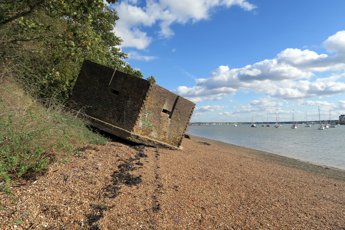 A pill box leans onto a shingle beach. Behind it is a steep wooded bank. The sea is blue and flat, about six metres from the pill box.