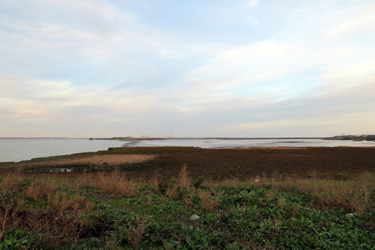 A Flat landscape of low marsh, the River Thames and a large muddy inlet known as Higham Creek