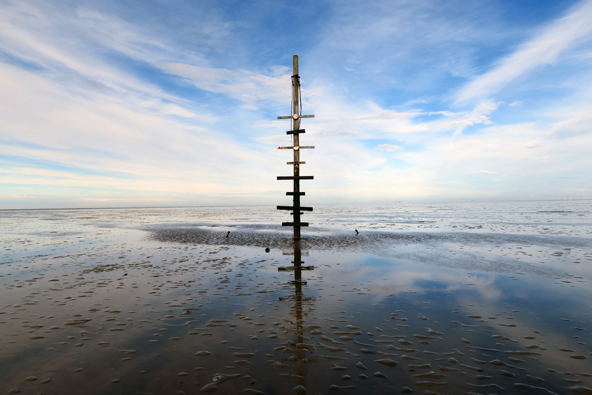 A tall pole with boards of wood of different lengths fastened across it