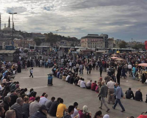 people in eminono in turkey sitting around the square