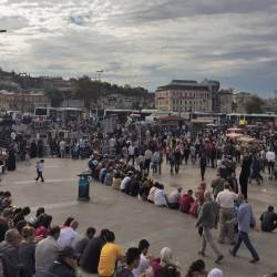 people in eminono in turkey sitting around the square