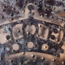 stamp of a crown on a rusty bronse plate