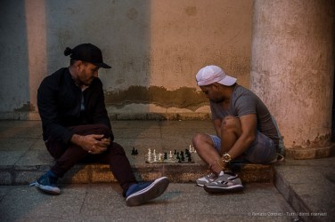 """Two friends throw a game of chess in the old town. Nikon D810, 70 mm (24-120.0 ƒ/4) 1/100"""" ƒ/4 ISO 3200."""