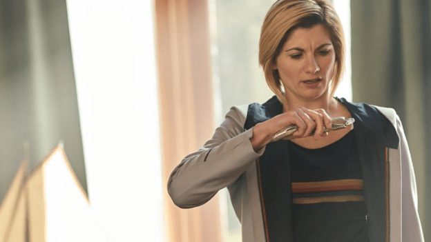 Jodie Whittaker as the Doctor reading information from off of her sonic screwdriver
