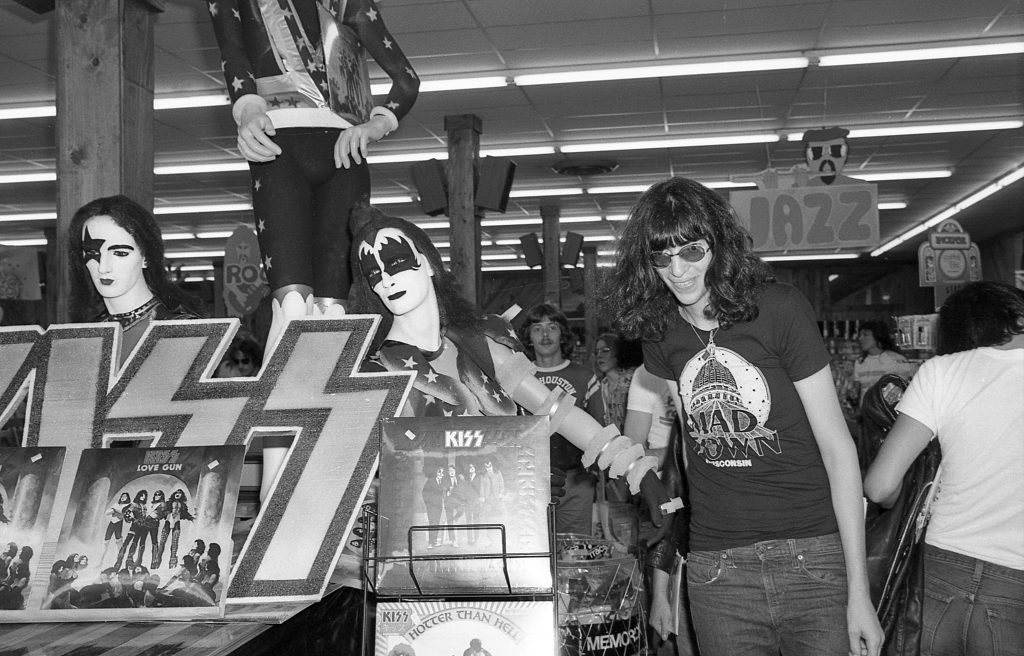 Jews for sale: Joey Ramone posing with a KISS stand in a record shop in Houston (1977). For what I know that 'KISS' logo has always been outlawed both in Israel and Germany obviously for containing the two SS runes in it. That is not the first time Jewish rock musicians steal National Socialist symbols. The band Blue Öyster Cult for instance (which, for what I gather, had at least three Jews in its line-up) caused uproar in the Jewish communities of their native Long Island for sporting iron crosses and all sorts of 'dangerous' regalia back in the early seventies. These were times of gratuitous rock gimmicks though just for shock value.