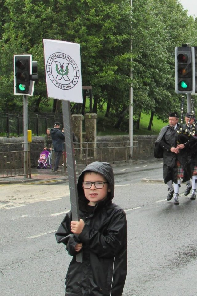 Young boy marching up the Thorn Brae with a banner
