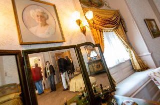 Guests are seen in a mirror under a portrait of Mary Vail Flyer, mother of Gertrude Hotchkiss, as they take tour the completely restored Hotchkiss Bedroom inside the Hotchkiss-Fyler House Museum at the Torrington Historical Society on Thursday. Jim Shannon Republican-American