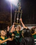WATERBURY, CT. 07 November 2019-110719BS02 - Holy Cross' Alyssa Hebb (16) raises the trophy high celebrating with her teammates after Holy Cross came from two goals down to beat Watertown 3-2, during the NVL Girls Soccer final between Holy Cross and Watertown at Municipal Stadium on Thursday. Bill Shettle Republican-American