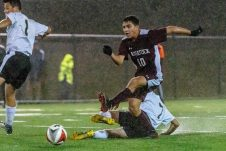WATERBURY, CT. 07 November 2019-110719BS576 - Naugatuck's Ahmed Aljamal (10), clears the ball away from a sliding Devon Polletta (7) of Woodland, during the NVL Boys Soccer final between Naugatuck and Woodland at Municipal Stadium on Thursday. Naugatuck beat Woodland 2-1. Bill Shettle Republican-American