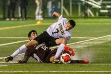 WATERBURY, CT. 07 November 2019-110719BS576 - Naugatuck's Mateus Filho (54) trips up Woodland's Devon Polletta (7) by trying to knock the ball away from him, during the NVL Boys Soccer final between Naugatuck and Woodland at Municipal Stadium in Waterbury on Thursday. The Naugatuck boys soccer team are the 2019 NVL Champions after beating Woodland 2-1. Bill Shettle Republican-American