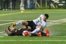 WATERBURY, CT. 07 November 2019-110719BS576 - Woodland's Devon Polletta (7) falls to the ground after being tripped up by Naugatuck's Mateus Filho (54), during the NVL Boys Soccer final between Naugatuck and Woodland at Municipal Stadium in Waterbury on Thursday. The Naugatuck boys soccer team are the 2019 NVL Champions after beating Woodland 2-1. Bill Shettle Republican-American