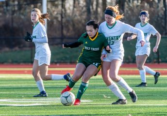 WATERBURY, CT. 16 November 2019-111619BS477 - Holy Cross' Delia Murphy (11), left, battles with Coventry's Morgan Eaton (13), during a Class S quarterfinal match between Coventry and Holy Cross at Crosby High School in Waterbury on Saturday. Holy Cross beat Coventry 3-0 and advances to the Class S semi-finals next week. Bill Shettle Republican-American