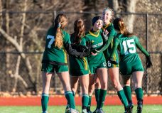 WATERBURY, CT. 16 November 2019-111619BS483 - Holy Cross teammates from left, Sophia Vescera (7), Mya Zaccagnini (26), Alyssa Hebb (16) and Jenna Debiase (15), all rush in to celebrate with Holy Cross' Devon Bushka (13), after she scored a goal, during a Class S quarterfinal match between Coventry and Holy Cross at Crosby High School in Waterbury on Saturday. Holy Cross beat Coventry 3-0 and advances to the Class S semi-finals next week. Bill Shettle Republican-American
