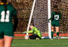 WATERBURY, CT. 16 November 2019-111619BS486 - Holy Cross goalkeeper Tori Schaffner (24) makes a save preserving her shutout with teammate Devon Bushka (13) nearby, during a Class S quarterfinal match between Coventry and Holy Cross at Crosby High School in Waterbury on Saturday. Holy Cross beat Coventry 3-0 and advances to the Class S semi-finals next week. Bill Shettle Republican-American