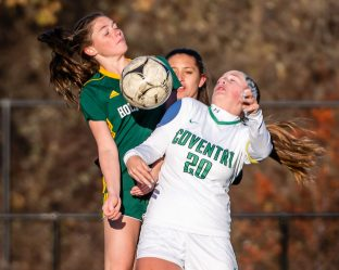 WATERBURY, CT. 16 November 2019-111619BS481 - Holy Cross' Ella Atkins (21), left, and Coventry's Shannon McKeon (20) try controlling the ball using their bodies as Holy Cross' Maeve Perrone (12) peaks in from behind, during a Class S quarterfinal match between Coventry and Holy Cross at Crosby High School in Waterbury on Saturday. Holy Cross beat Coventry 3-0 and advances to the Class S semi-finals next week. Bill Shettle Republican-American