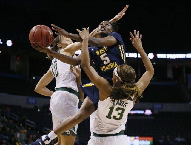 FILE - In this March 6, 2017, file photo, West Virginia guard Tynice Martin (5) shoots between Baylor guard Alexis Prince (12) and forward Nina Davis (13) in the first half of an NCAA college basketball championship game at the Big 12 Conference tournament in Oklahoma City. West Virginia coach Mike Carey was happy to have Martin and Kysre Gondrezick back this season to give his team more depth after only having seven players last year. (AP Photo/Sue Ogrocki, File)