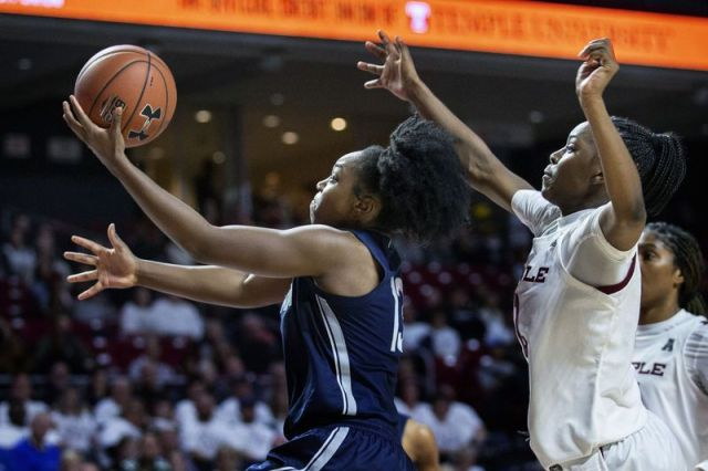 Connecticut guard Christyn Williams, left, goes to the basket followed by Temple guard Asonah Alexander during the second half of an NCAA college basketball game Sunday, Nov. 17, 2019, in Philadelphia. Connecticut won 83-54. (AP Photo/Laurence Kesterson)