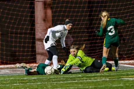 NAUGATUCK, CT. 20 November 2019-112019BS881 - Holy Cross goalkeeper Tori Schaffner (24) dives toward a loose ball after making a save on Litchfield's Christina Orsini (7) with Holy Cross' Alyssa Milburn (23) and Holy Cross' Alexa Diorio (3) defending, during the Girls Soccer Class S semifinal match between Litchfield and Holy Cross at Naugatuck High School on Wednesday. Holy Cross beat Litchfield 3-1 and advances to the Class S final this Saturday. Bill Shettle Republican-American