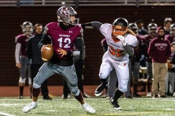 NAUGATUCK, CT. 21 November 2019-112119BS401 - Naugatuck's John Mezzo (12) looks to throw the ball downfield with Watertown's Jonathan Palomba (32) charging from behind, during a NVL Football game between Watertown and Naugatuck at Naugatuck High School on Thursday. Bill Shettle Republican-American