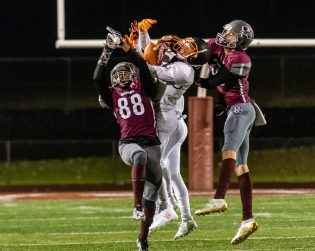 NAUGATUCK, CT. 21 November 2019-112119BS411 - Watertown's Leo Kolonsky (11), center, goes up and catches the ball in between Naugatuck's Louis Lugo (88) and Aiden Robertson (19), during a NVL Football game between Watertown and Naugatuck at Naugatuck High School on Thursday. Bill Shettle Republican-American