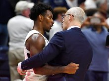 Connecticut's Christian Vital, left, is embraced by Connecticut head coach Dan Hurley at the end of an NCAA college basketball game against Florida, Sunday, Nov. 17, 2019, in Storrs, Conn. (AP Photo/Jessica Hill)