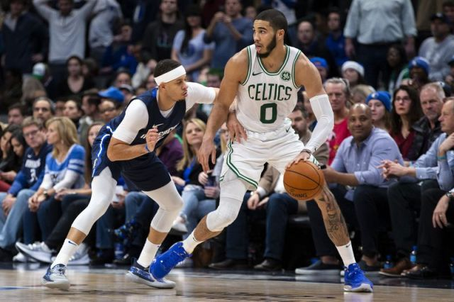 Boston Celtics forward Jayson Tatum (0) dribbles the ball as Dallas Mavericks guard Seth Curry (30) defends during the second half of an NBA basketball game Wednesday, Dec. 18, 2019, in Dallas. (AP Photo/Sam Hodde)