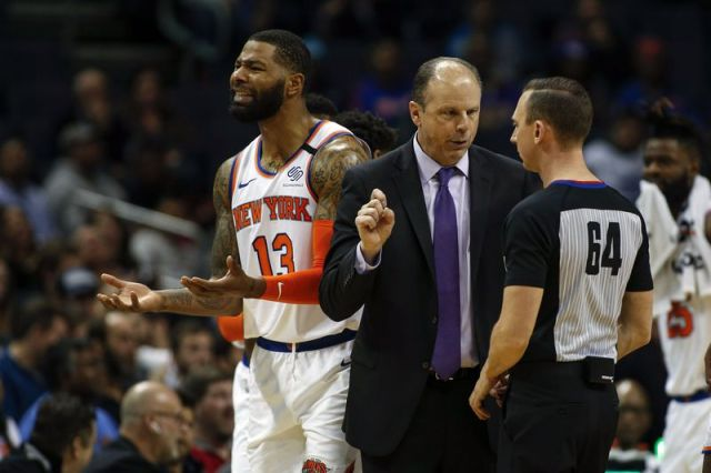 New York Knicks head coach Mike Miller, center, argues with NBA official Justin Van Duyne as New York Knicks forward Marcus Morris Sr. reacts to a call in the closing minutes of the second half of an NBA basketball game against the Charlotte Hornets in Charlotte, N.C., Tuesday, Jan. 28, 2020. Charlotte won 97-92. (AP Photo/Nell Redmond)