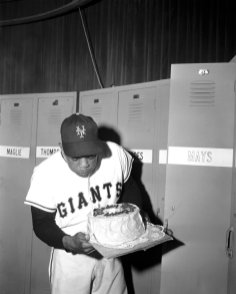 FILE - New York Giants centerfielder Willie Mays blows out a candle on a cake to celebrate his 24th birthday in the Polo Grounds club house after a night game with the Pittsburgh Pirates in New York, in this May 6, 1955, file photo. Mays turns 90 on Thursday, May 6, 2021. (AP Photo/Matty Zimmerman, File)