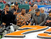 FILE - Willie Mays, right, uses his hand to chop through a large birthday cake presented in honor of his 75th birthday before the start of the San Francisco Giants baseball game against the Los Angeles Dodgers in San Francisco, in this Friday, May 12, 2006, file photo. Giants' Jose Vizcaino, left, laughs and former Giant and current broadcaster Tito Fuentes, center, applauds. Mays turns 90 on Thursday, May 6, 2021.(AP Photo/Eric Risberg, File)