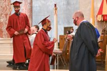Sacred Heart Athletic Director and teacher Mike Madden, right, gives a fist bump to graduate Mark Iannantuoni during the 99th annual commencement exercises for Sacred Heart High School Friday at The Basilica of the Immaculate Conception in Waterbury. Jim Shannon Republican American
