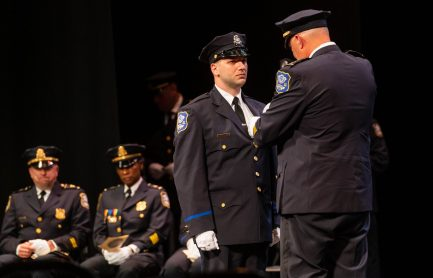 Waterbury Police Academy recruit Anthony Batista gets his badge pinned on him by Waterbury Police Chief Fernando Spagnolo during basic training graduation ceremonies for the Waterbury Police Academy Class 2021-01 Tuesday at the Palace Theater in Waterbury. Batista will become a member of the Waterbury Police Department. Jim Shannon Republican American